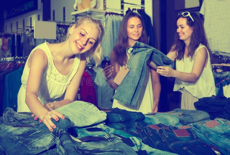 """ragazze del ¿ tre del ï"""" che scelgono i pantaloni del denim fotografia stock"""