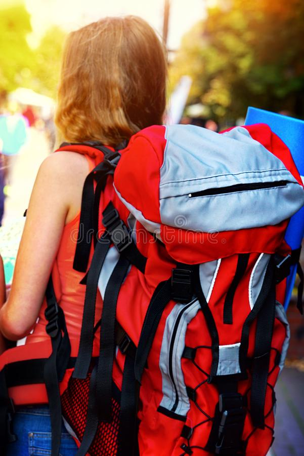 Ragazze del viaggiatore con la fine posteriore di vista sullo zaino femminile rosso immagine stock