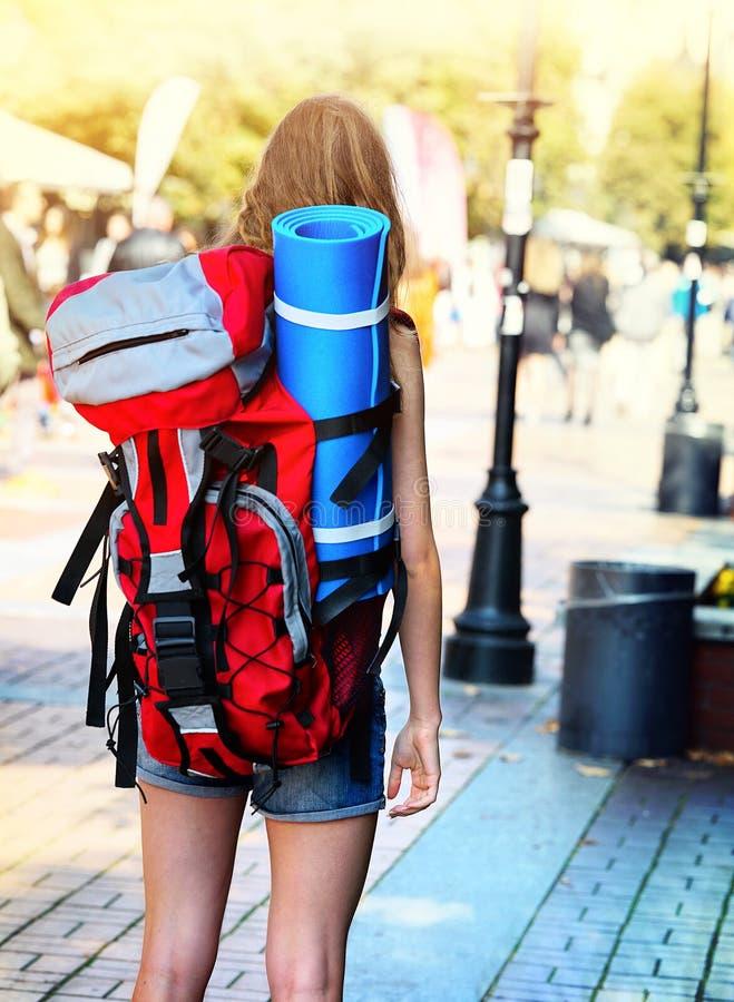 Ragazze del viaggiatore con la fine posteriore di vista sullo zaino femminile rosso fotografia stock