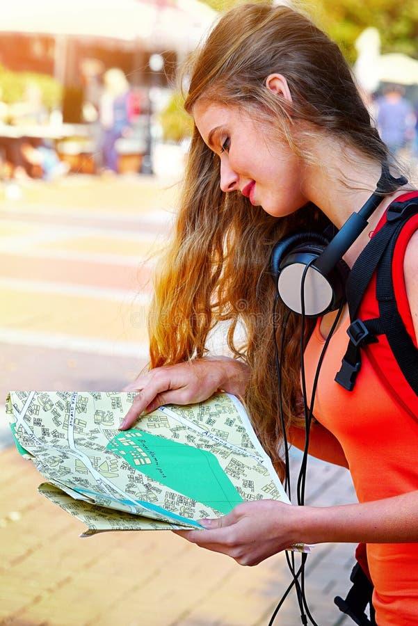 Ragazze del viaggiatore con lo zaino che cerca la mappa di carta turistica di modo immagini stock libere da diritti