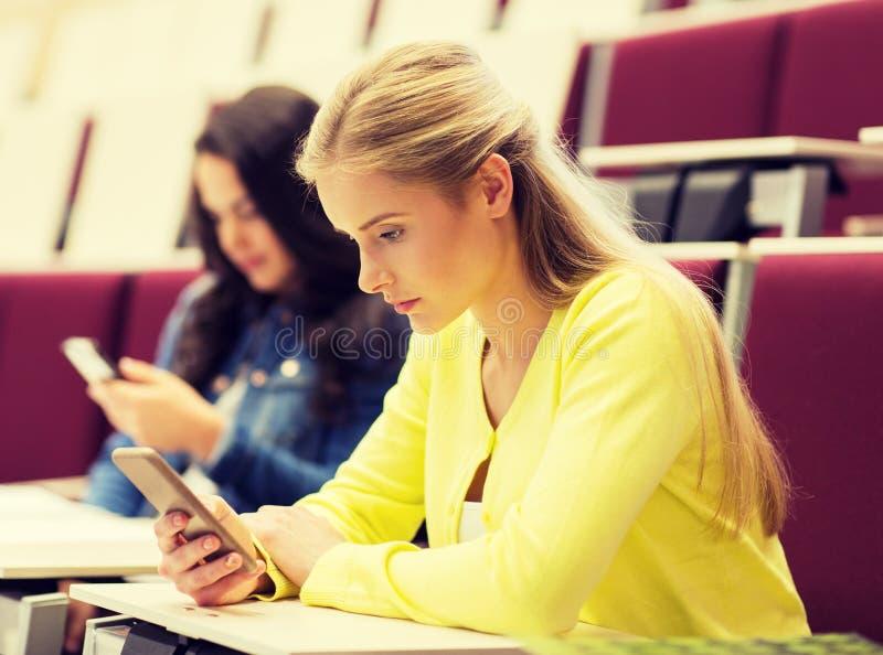 Ragazze dello studente con gli smartphones sulla conferenza fotografie stock libere da diritti