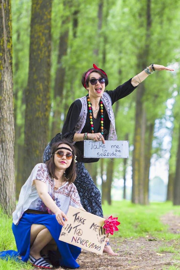 Ragazze di hippy che fanno auto-stop fotografie stock
