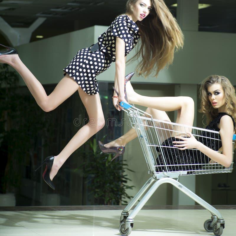 Ragazze divertenti con il carrello di acquisto fotografie stock libere da diritti