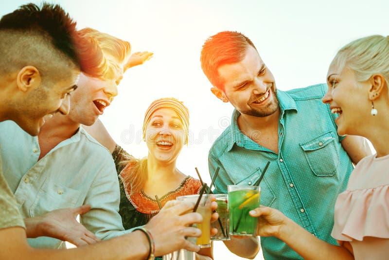 Ragazze e ragazzi sorridenti della gente del partito, uomini e donne beventi i cocktail fuori immagini stock
