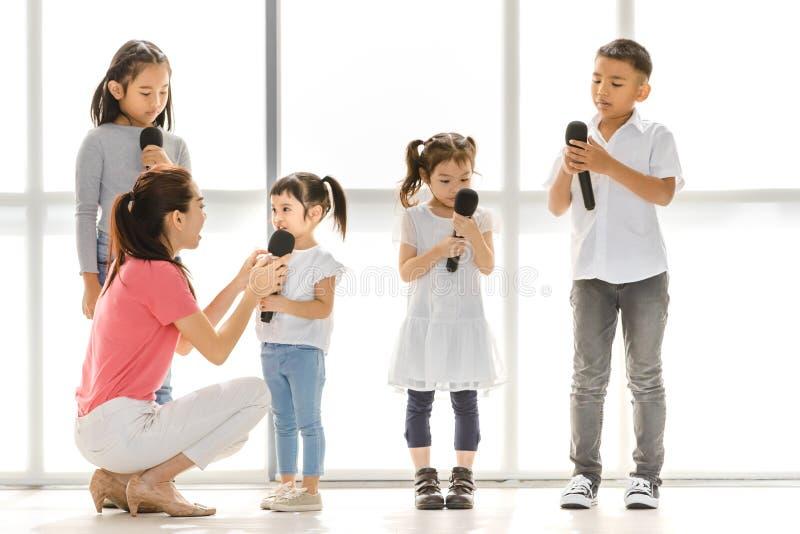 Ragazze e ragazzo asiatici del gioco dell'insegnante certo agire immagine stock libera da diritti
