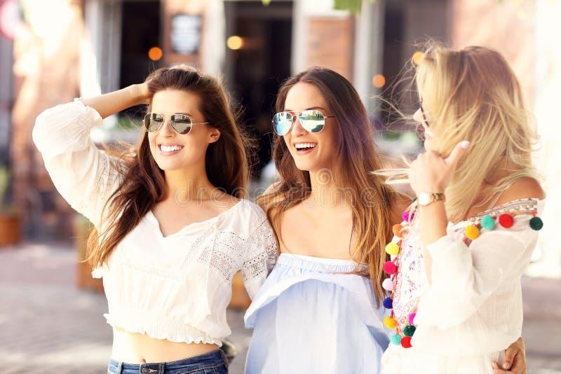 Ragazze felici che vanno in giro nella città di estate fotografie stock