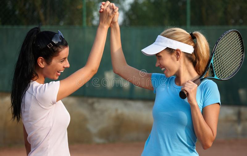 Ragazze felici sulla corte di tennis immagini stock