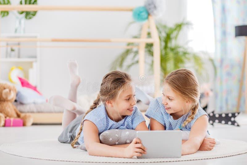 Ragazze gemellate che dividono una compressa immagine stock