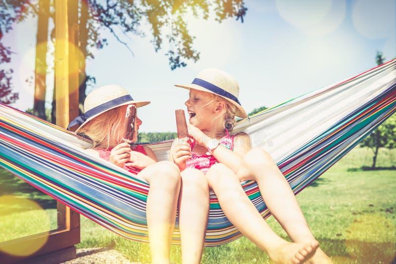 Ragazze in hammock che mangiano il gelato fotografie stock libere da diritti