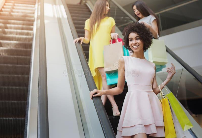 Ragazze multirazziali felici sulla scala mobile in centro commerciale fotografie stock