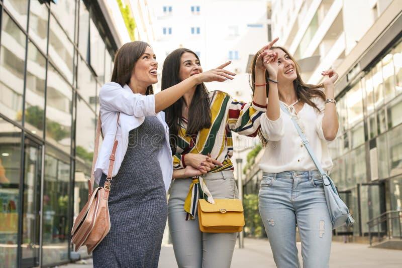 Ragazze sorridenti che camminano sulla via con i sacchetti della spesa ragazza s fotografia stock
