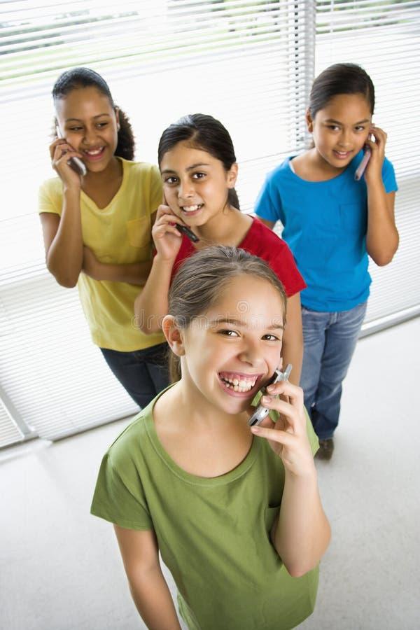 Ragazze sui telefoni delle cellule. immagine stock