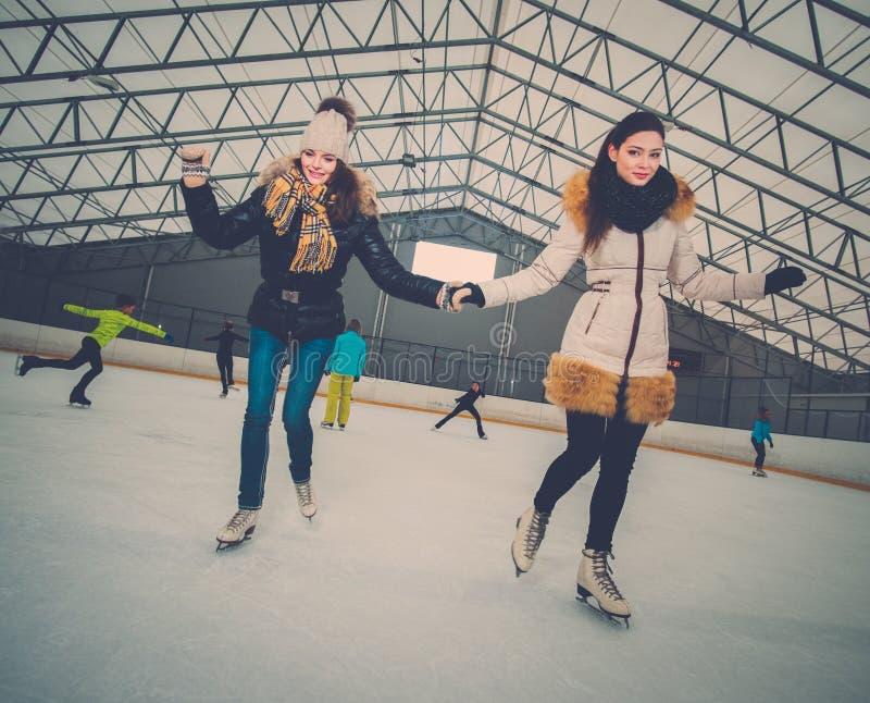 Ragazze sulla pista di pattinaggio di pattinaggio sul ghiaccio immagini stock libere da diritti