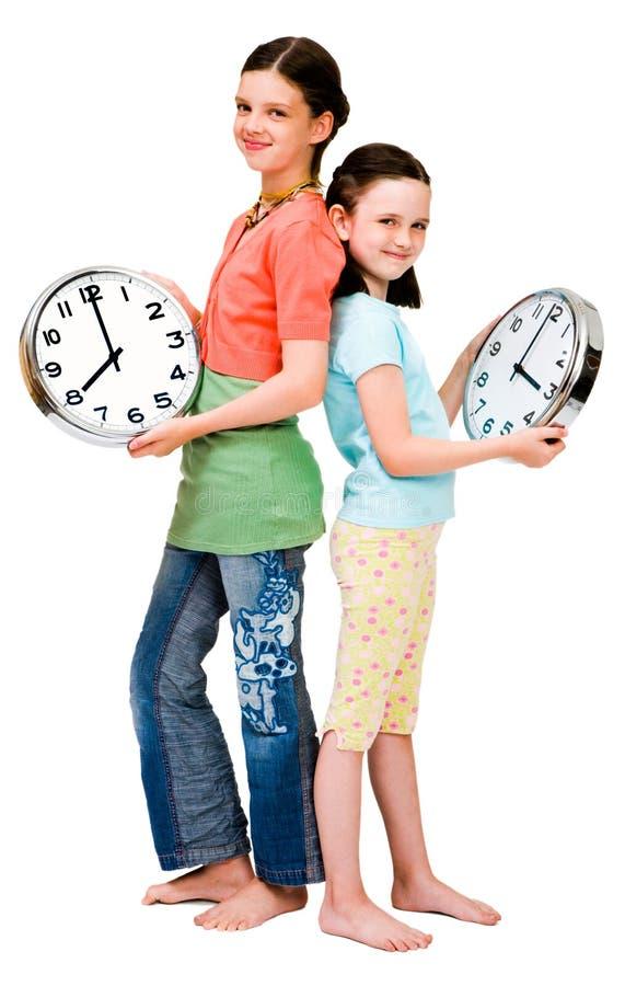 Ragazze sveglie che tengono gli orologi immagini stock libere da diritti