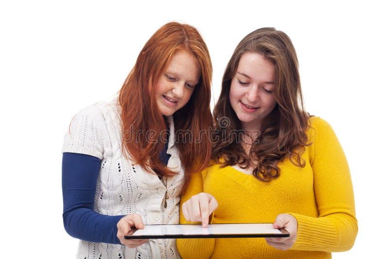 Ragazze teenager con il computer della compressa immagini stock
