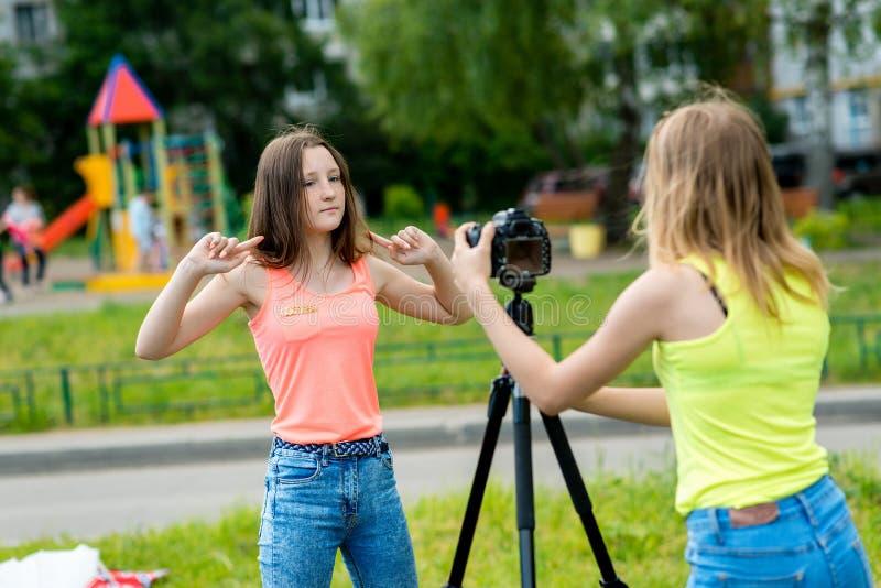 2 ragazze teenager Estate in natura Gestures emozionalmente Balli alla macchina fotografica Abbonati record del blog e del vlog r immagini stock