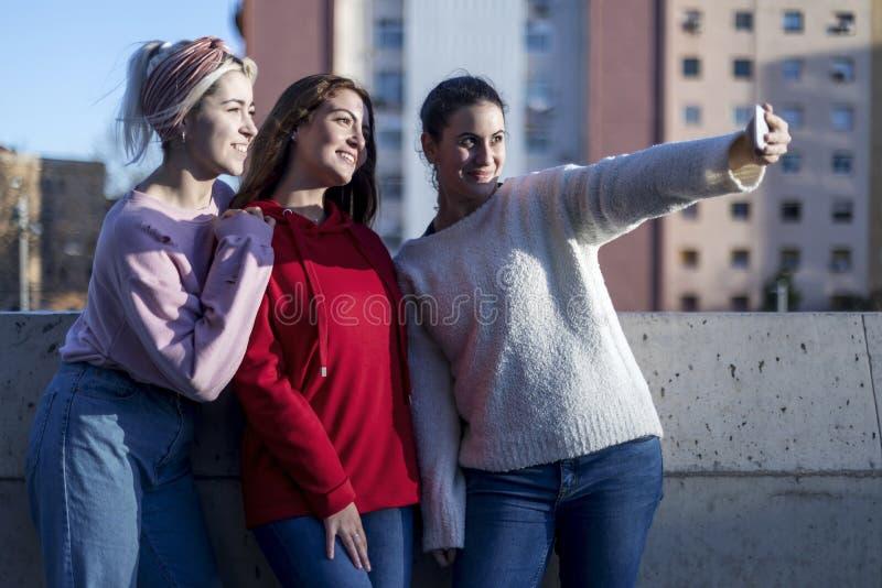 Ragazze teenager felici che prendono selfie in parco con il telefono cellulare all'aperto fotografia stock