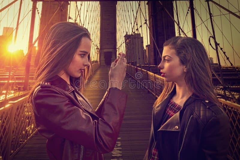 Ragazze turistiche teenager che prendono foto in ponte di Brooklyn NY immagine stock