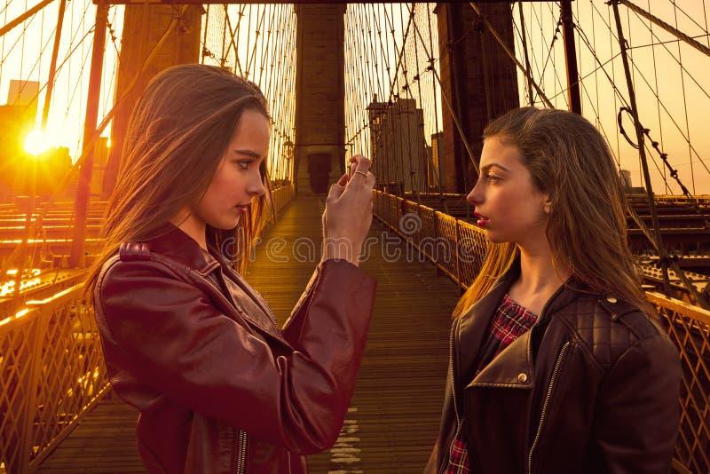 Ragazze turistiche teenager che prendono foto in ponte di Brooklyn NY fotografia stock