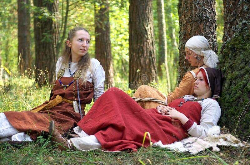 Ragazze in vecchio vestito nazionale russo che si siede nel legno fotografia stock libera da diritti