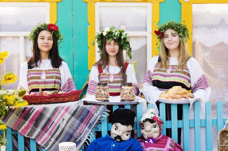 Ragazze in vestiti pieghi russi, con le corone sulle loro teste immagine stock