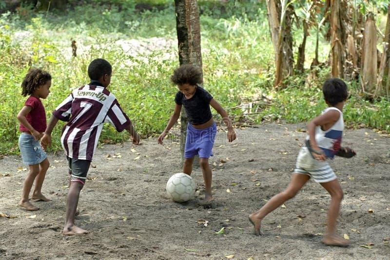 Ragazzi brasiliani e ragazze che giocano a calcio nel calore tropicale fotografie stock