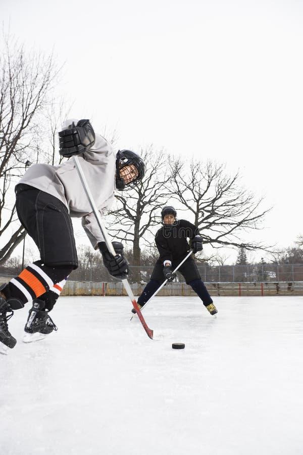 Ragazzi che giocano il hokey di ghiaccio. immagini stock libere da diritti