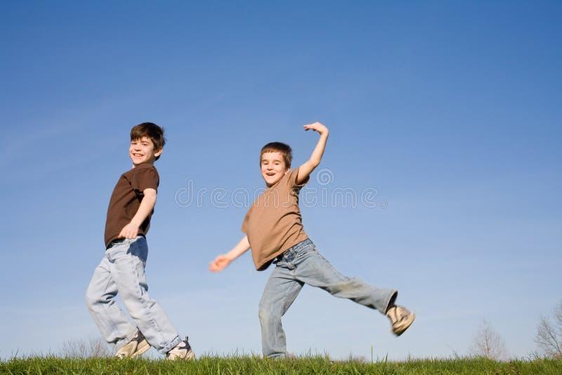 Ragazzi che giocano su una collina fotografia stock libera da diritti