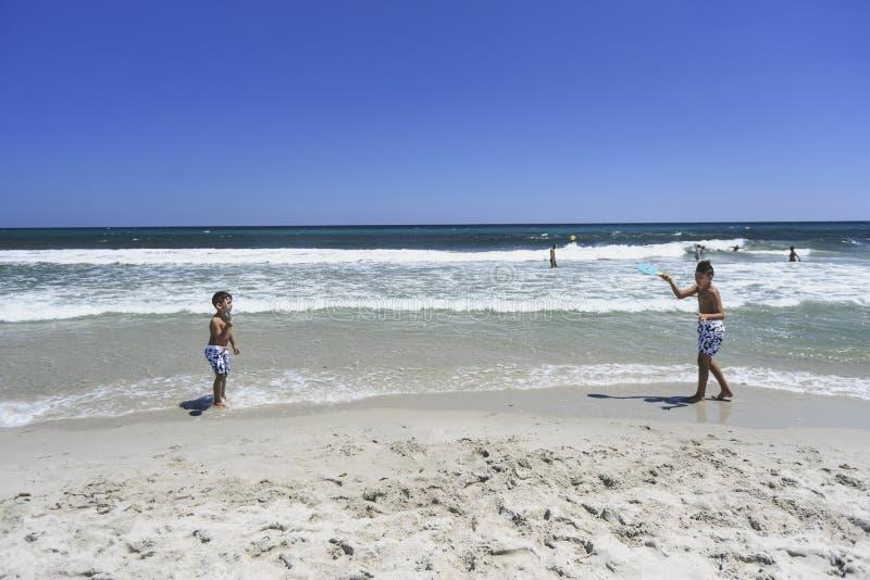 Ragazzi che giocano a tennis sulla spiaggia fotografia stock libera da diritti