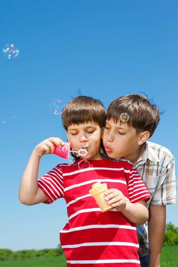 Ragazzi che saltano le bolle fotografie stock