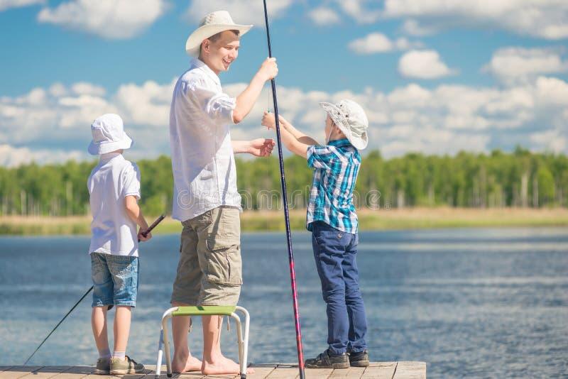 Ragazzi con suo padre sul pilastro mentre pescando immagini stock libere da diritti