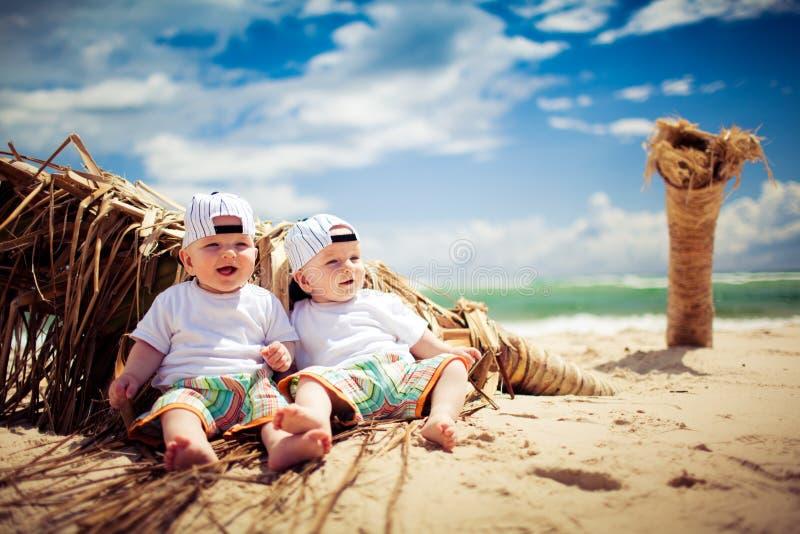 Ragazzi del gemello identico che si distendono su una spiaggia fotografia stock