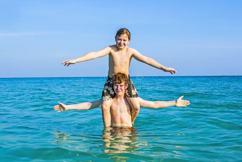 Ragazzi divertendosi gioco sulle spalle nell'oceano caldo immagine stock