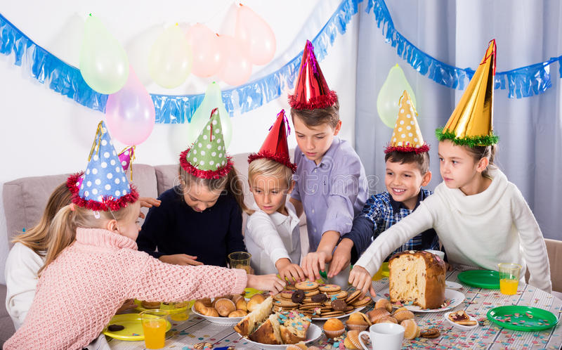 Ragazzi e ragazze gioiosi cenando al compleanno fotografia stock libera da diritti