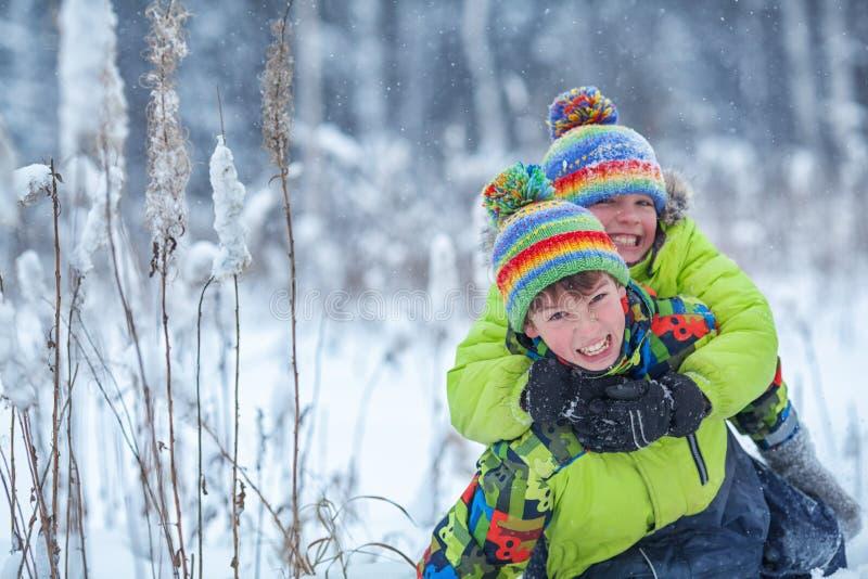 Ragazzi felici allegri che giocano nel parco di inverno, fotografia stock libera da diritti