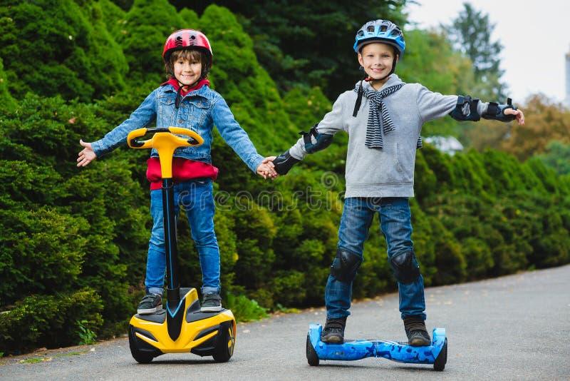 Ragazzi felici che guidano sui hoverboards o gyroscooters all'aperto immagini stock libere da diritti