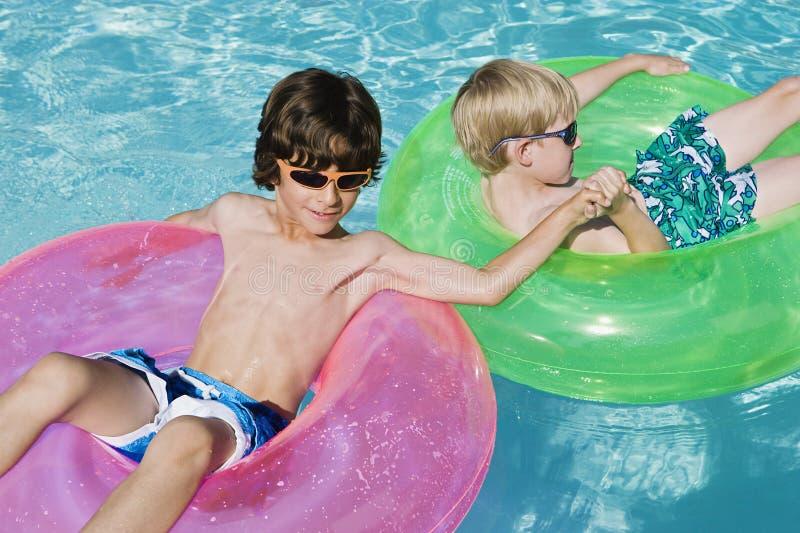 Ragazzi sui tubi del galleggiante nella piscina fotografia stock