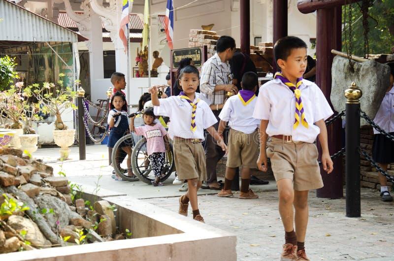 Ragazzi tailandesi degli studenti ed esploratori di ragazze che camminano la statua pregante di Buddha di rispetto e di visita a  fotografia stock