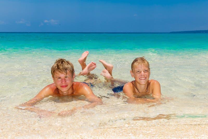 Ragazzi teenager felici che si rilassano sulla spiaggia Mare tropicale nel backg fotografia stock libera da diritti