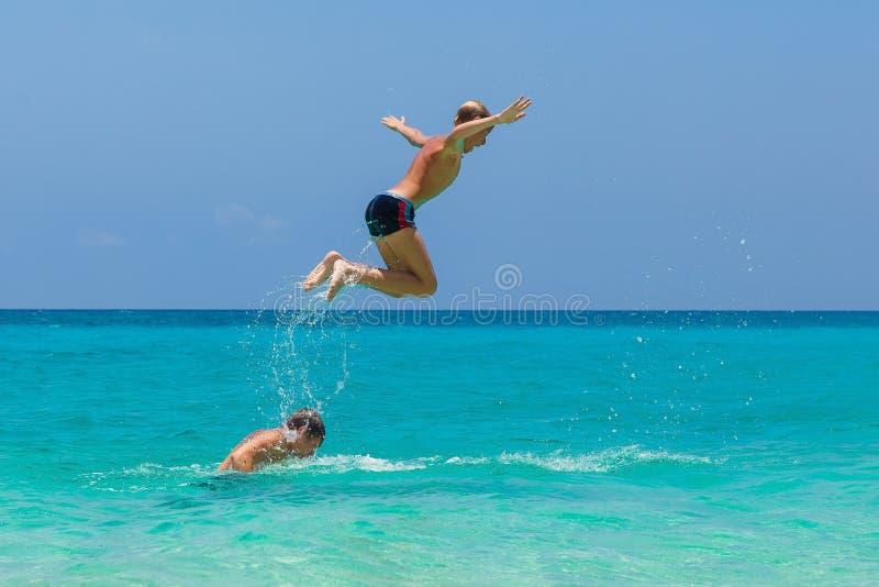 Ragazzi teenager felici divertendosi sulla spiaggia tropicale Vacatio di estate immagini stock