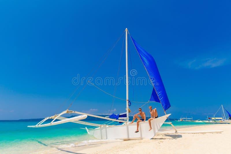 Ragazzi teenager felici sulla barca a vela sulla spiaggia tropicale Estate va fotografie stock libere da diritti