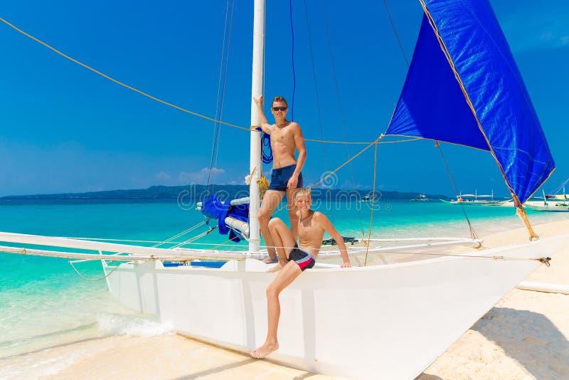 Ragazzi teenager felici sulla barca a vela sulla spiaggia tropicale Estate va fotografia stock libera da diritti