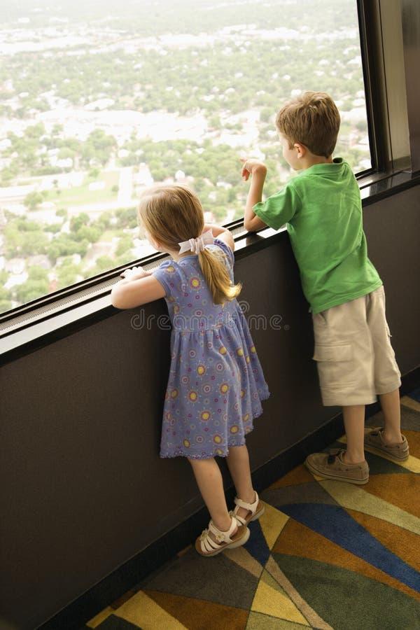 Ragazzini alla finestra. fotografie stock libere da diritti