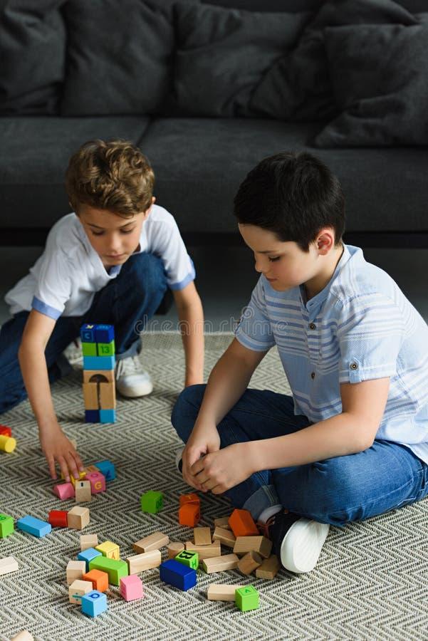 ragazzini che giocano con i blocchi di legno sul pavimento fotografia stock libera da diritti