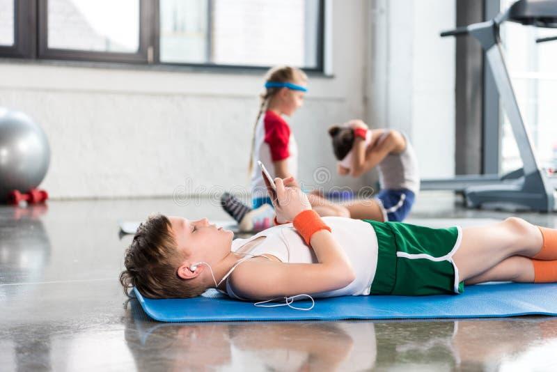 Ragazzini che si trovano sulla stuoia di yoga e che utilizzano smartphone mentre amici che si esercitano nella palestra fotografie stock