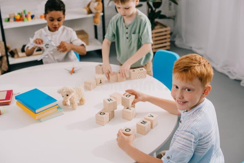 ragazzini multiculturali che maneggiano con i blocchi di legno alla tavola immagini stock libere da diritti