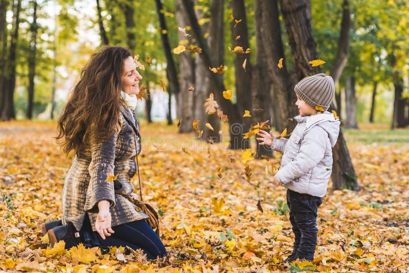 Ragazzino adorabile con sua madre nel parco di autunno fotografia stock libera da diritti