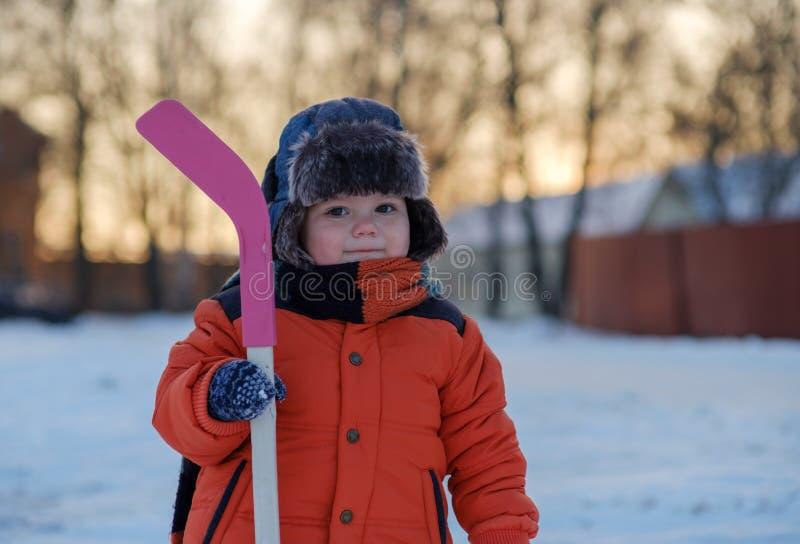 Ragazzino adorabile con un bastone di hockey su una passeggiata nell'inverno immagine stock