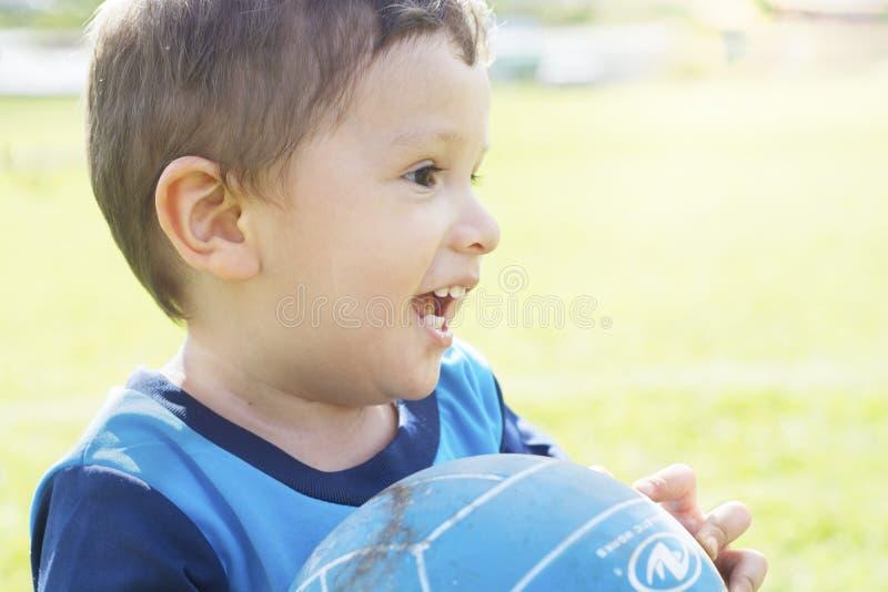 Ragazzino allegro che gioca all'aperto con una palla fotografia stock