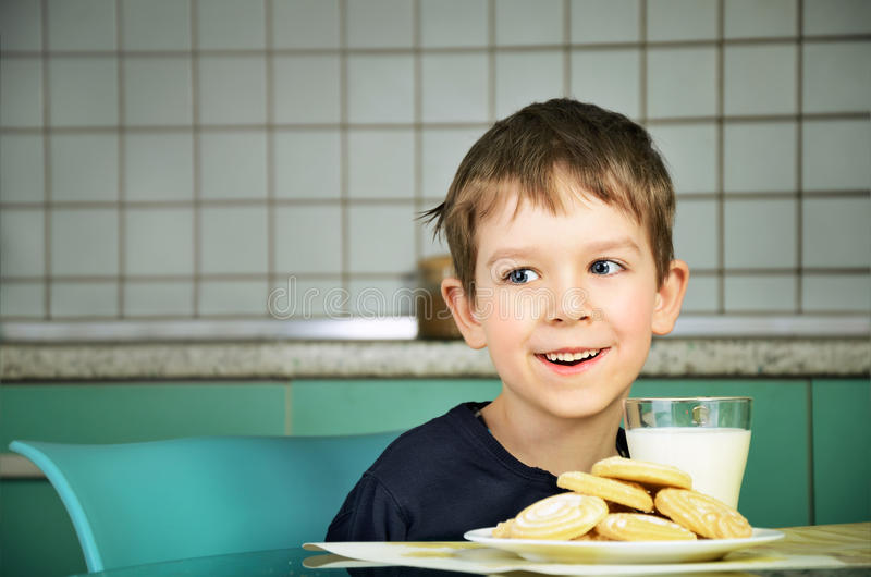 Ragazzino allegro sorridente che si siede alla tavola di cena horizo immagine stock
